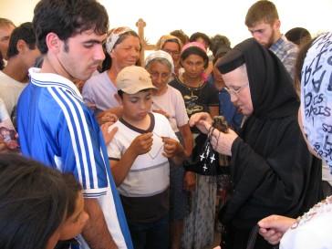 Maica Siluana impartind cruciulite copiilor de la Rast